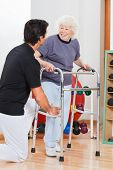 image of zimmer frame  - Happy senior woman with walker looking at trainer - JPG