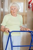 stock photo of zimmer frame  - Portrait of a senior woman in hospital using Zimmer frame - JPG