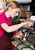 Friendly waitress making coffee at coffee machine