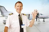 Airline pilot wearing uniform with epaulettes waving, with passenger aircraft in background
