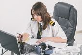 Beautiful woman pilot wearing uniform with epaulettes doing preflight briefing poster