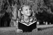 Little Child Reading Book Outdoors. Schoolgirl Reading Stories While Relaxing Green Lawn. Cute Pupil poster