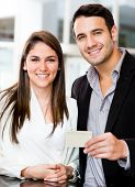 Couple holding a credit or debit card and smiling