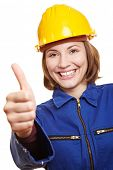 Cheering happy craftswoman in blue boiler suit holding thumbs up