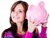 Woman holding a piggybank and smiling - isolated over white