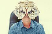 Caucasian Man  Checks Eyesight In A Clinician Oculist. Man Checks His Vision On The Machine Checking poster