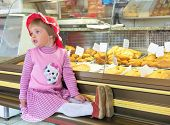 picture of bakeshop  - Beautiful little girl sitting in the bakery shop - JPG