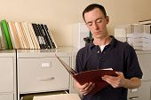 Caucasian male in file room reading papers inside a folder