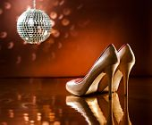 stock photo of stiletto heels  - Beautiful brown stilettos on the dance floor with mirror ball - JPG
