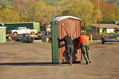 pic of porta-potties  - Porta Pottie portable toilet being moved by two people - JPG