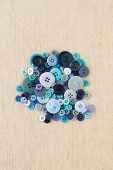 Pile Of Blue Buttons On Hessian