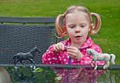 Little Girl Playing With Toy Horses