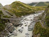 Swing bridge over mountain river in New Zealand