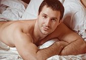 Young sexy muscular man in a bed