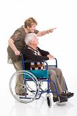 cheerful senior woman pointing while her disabled husband on wheel chair