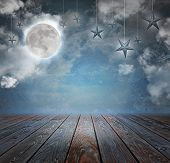 stock photo of twinkle  - A moon and stars are in the night sky with wood on the bottom copyspace area to add your text message - JPG