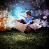pic of boys night out  - A young boy is sitting in a cardboard box and floating in the night sky reaching for a star in space - JPG