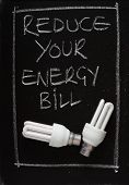 stock photo of economizer  - Reduce Your Energy Bill written on a blackboard with two energy efficient light bulbs - JPG