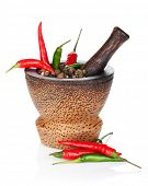 Mortar and pestle with red hot chili pepper and peppercorn. Isolated on white background