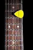 stock photo of reggae  - Yellow guitar pick on the fingerboard close up isolated on black background - JPG