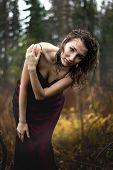 Portrait of woman im purple dress under rain
