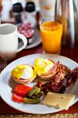 Delicious breakfast with eggs Benedict, bacon, orange juice and coffee