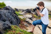 Little boy photographing marine iguanas on volcanic rocks