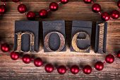The word NOEL written with vintage wood printer blocks. Christmas message over old wood with a strin