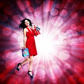 Young woman with shopping bags over glowing background.