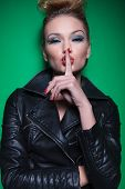 fashion woman with nice makeup and hairstyle is covering her mouth with her finger making the quiet