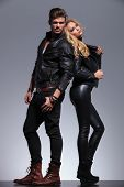 young fashion couple in leather clothes standing back to back