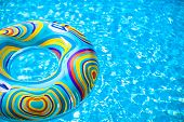 Inflatable Colorful Rubber Ring Floating In Blue Swimming Pool