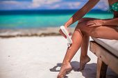 Young Woman Apply Cream On Her Smooth Tanned Legs At Tropical Beac