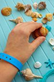 picture of all-inclusive  - Female hand with all inclusive bracelet holding seashells on a blue background - JPG