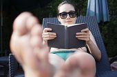 Young woman in sunglasses and swimsuit relaxing and reading book