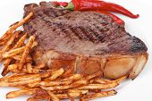 entree : grill beef meat steak on white round plate with dry hot chili pepper and potato chips isola