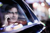 picture of car-window  - Businessman on the phone and looking out car window at night - JPG