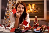 Woman arranging christmas gifts by fireplace, holding gift tag with male names, thinking, smiling, l