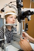Preadolescent boy having his eyes examined with slit lamp by doctor