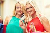 sale and tourism, happy people concept - beautiful women with shopping bags and credit card in the c