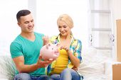 moving, home and couple concept - smiling couple with piggybank in new home