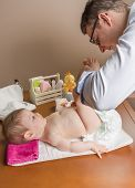 picture of diaper change  - Father changing diaper of adorable baby with a hygiene set for babies on the background - JPG