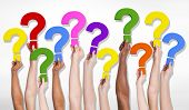 Multi-Ethnic group of human hands holding question marks.