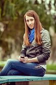 Attractive Trendy Young Woman Sitting On A Bench