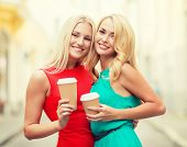 holidays and tourism, friends, blonde girls concept - beautiful women with takeaway coffee cups in t