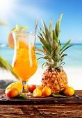 Fresh summer orange drink, blur beach on background