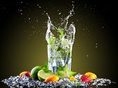 Studio shot of fresh mojito drink with ice cubes and splash on black background