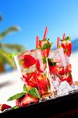 Fresh summer strawberry mojito drinks with ice, blur beach on background