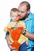 Bright studio portrait of young modern father and his small son with yellow tulips on isolated white