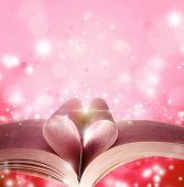 Pages of book in shape of love heart in front of magical background